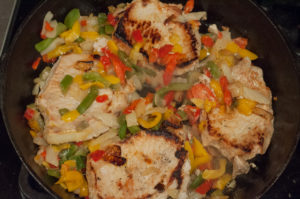 Easy Skillet Peppers, Onions and Pork Chops from Farmwife Feeds is an easy meal using frozen pepper and onion mix and boneless pork chops. #pork #recipe #porkchops